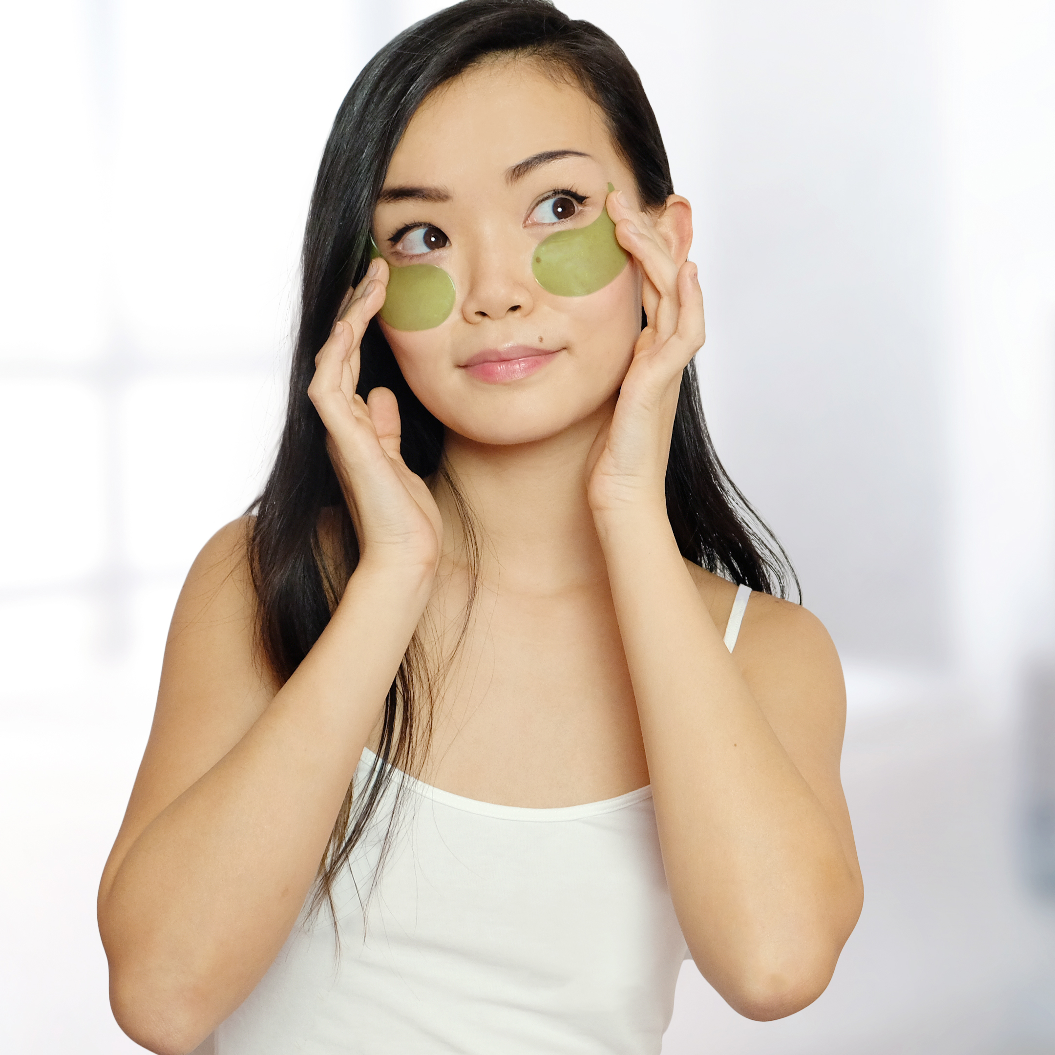 A model applies both green patches under their eyes